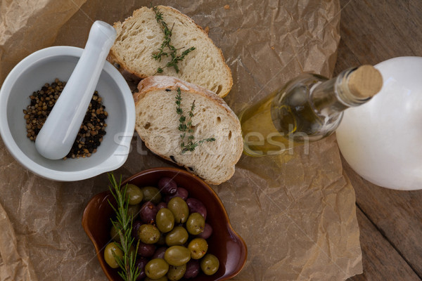 Directly above shot of olives with oil bottle and bread by spices in mortar pestle on crumbled paper Stock photo © wavebreak_media
