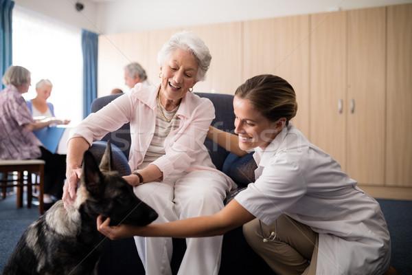 Portrait of smiling female doctor kneeling by senior woman stroking puppy Stock photo © wavebreak_media