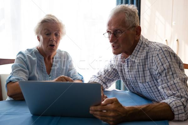Senior man showing laptop to female friend in nursing home Stock photo © wavebreak_media
