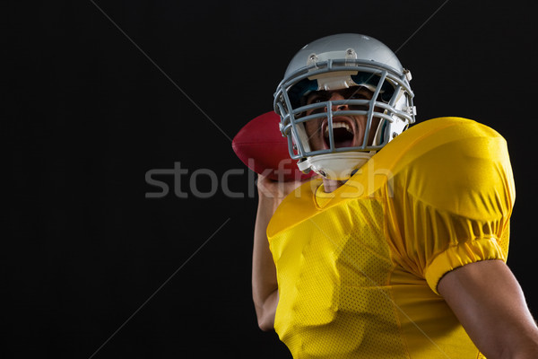 Energetic American football player holding a ball in one hand Stock photo © wavebreak_media