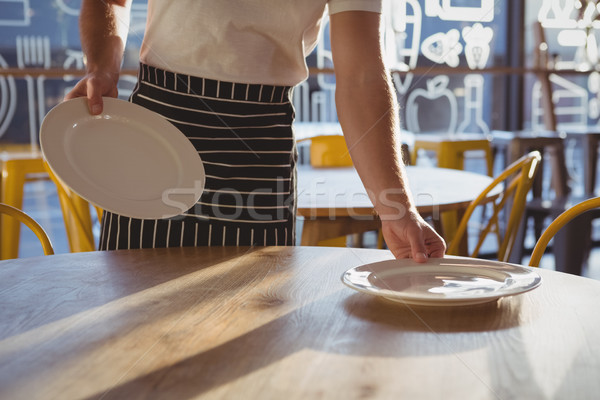 Mid section of waiter arranging plates on table Stock photo © wavebreak_media