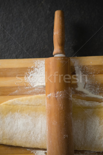 Close up of rolling pin on dough over cutting board Stock photo © wavebreak_media