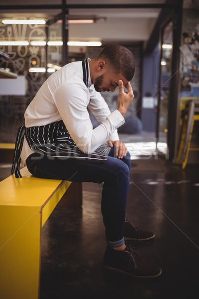 Side view of upset young waiter sitting on yellow bench with headache Stock photo © wavebreak_media