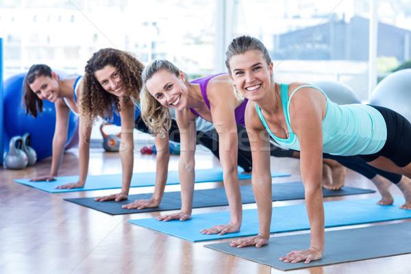Cheerful women doing plank pose in fitness studio Stock photo © wavebreak_media