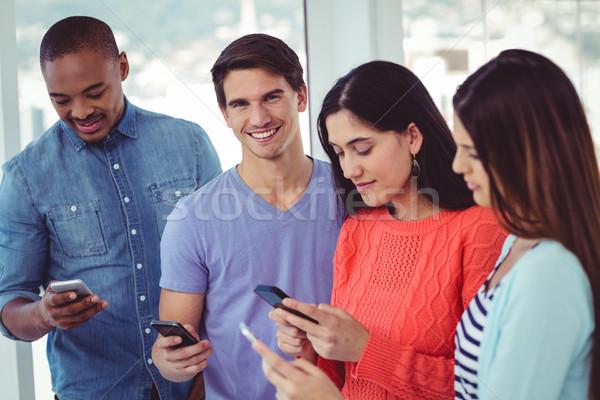 Fiatal kreatív csapat néz telefonok lezser Stock fotó © wavebreak_media