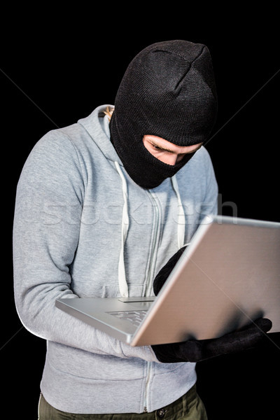 Focused thief with hood typing on laptop Stock photo © wavebreak_media