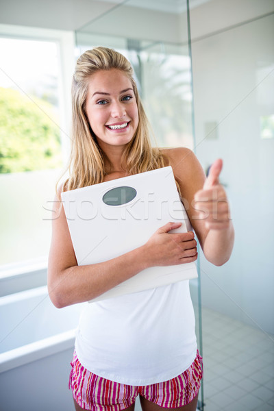 Woman holding a weighting scale with thumbs up Stock photo © wavebreak_media