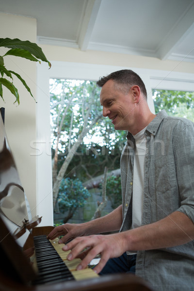 Stock photo: Man playing piano at home