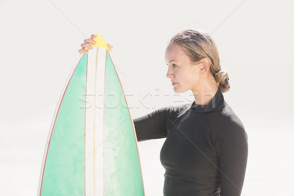 Woman in wetsuit holding a surfboard Stock photo © wavebreak_media