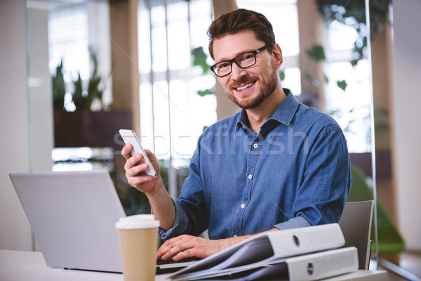 Portrait of confident executive using cellphone at creative offi Stock photo © wavebreak_media