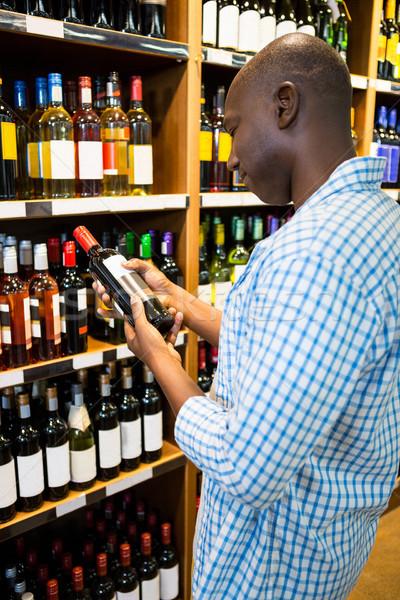 Homem olhando garrafa de vinho mercearia seção supermercado Foto stock © wavebreak_media