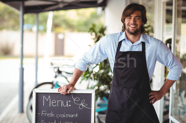 Waiter standing with menu board outside the cafe Stock photo © wavebreak_media