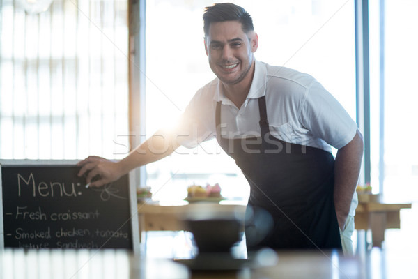 Smiling waiter writing on menu board in cafe Stock photo © wavebreak_media