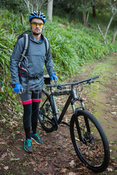 Portrait of male mountain biker with bicycle in the forest Stock photo © wavebreak_media