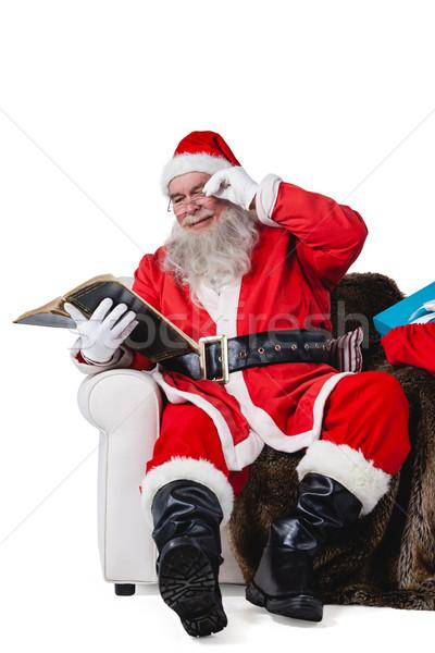 Santa reading bible with sack of christmas present beside him Stock photo © wavebreak_media