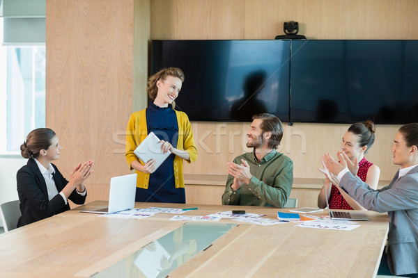 Business team applauding their colleague in conference room Stock photo © wavebreak_media