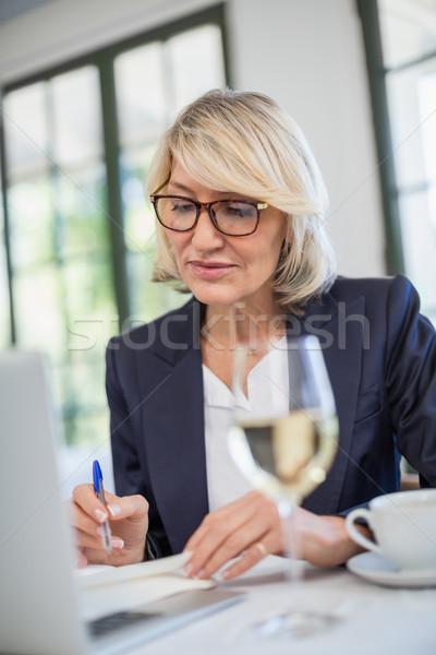Femme d'affaires écrit journal restaurant attentif affaires Photo stock © wavebreak_media