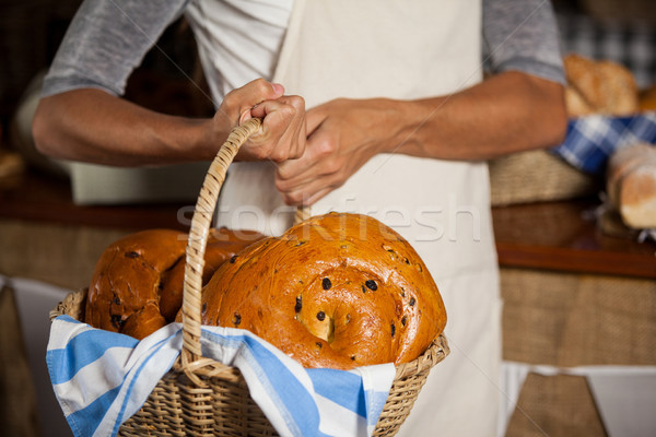 Mid-section of female staff holding wicker basket of breads at counter Stock photo © wavebreak_media