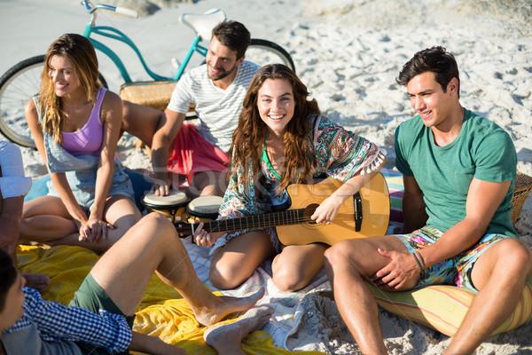 Friends enjoying while sitting at beach Stock photo © wavebreak_media
