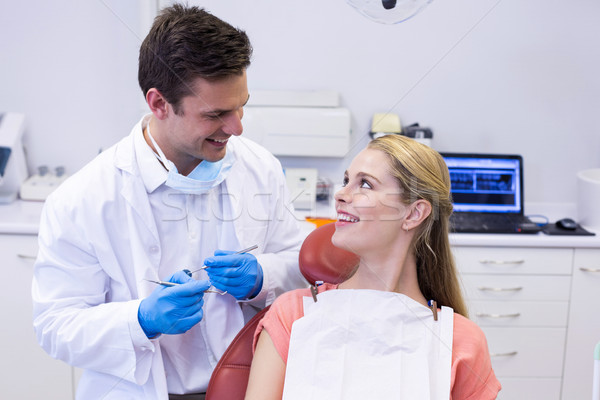 Dentist interacting with female patient while examining Stock photo © wavebreak_media