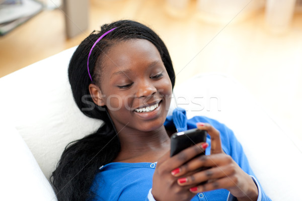 Radiant woman sending a text lying on a sofa Stock photo © wavebreak_media