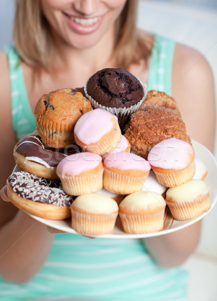 Blond woman holding a plate of cakes Stock photo © wavebreak_media
