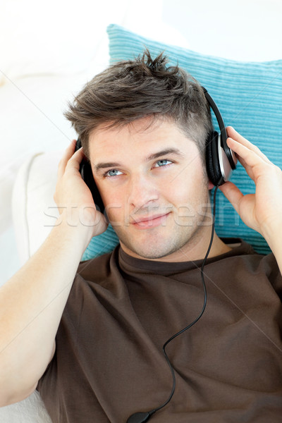 Smiling young man with headphones listening to music lying on a sofa Stock photo © wavebreak_media