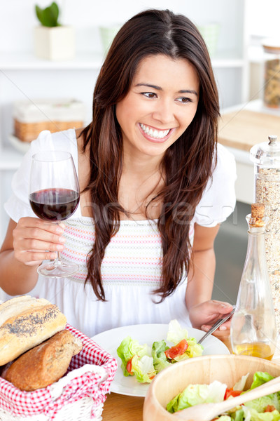Captivating asian woman holding a wineglass eating a salad at home in the kitchen Stock photo © wavebreak_media