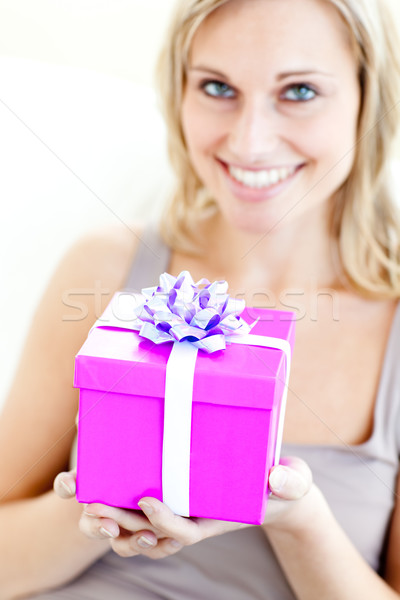 Charming woman holding a present in front of her against a white background Stock photo © wavebreak_media