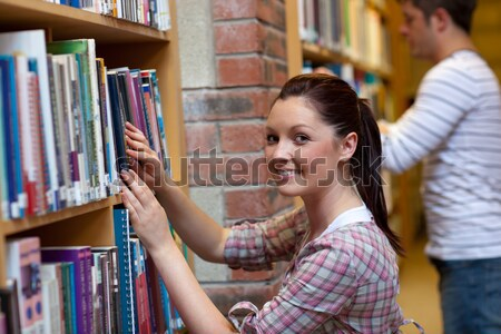 Pretty young woman looking for a book in a bookstore Stock photo © wavebreak_media