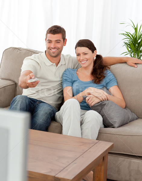 Happy man changing channel while watching television with his wife at home Stock photo © wavebreak_media