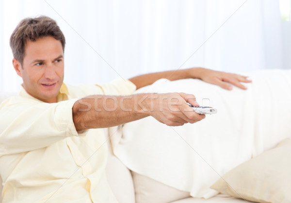 Handsome man changing channel sitting on the sofa Stock photo © wavebreak_media