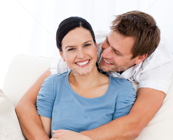 Passionate man hugging his girlfriend while relaxing on the sofa at home Stock photo © wavebreak_media