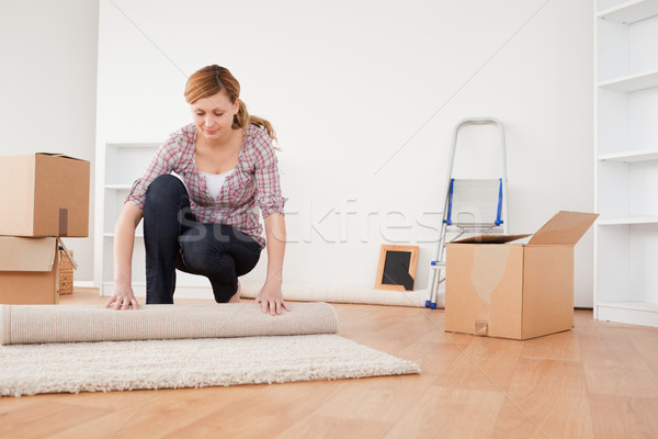 Lovely woman rolling up a carpet to prepare to move house  Stock photo © wavebreak_media