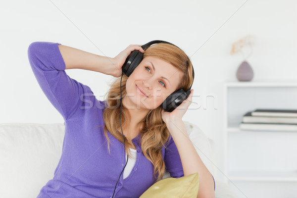 Attractive red-haired woman listening to music and enjoying the moment while sitting on a sofa in th Stock photo © wavebreak_media