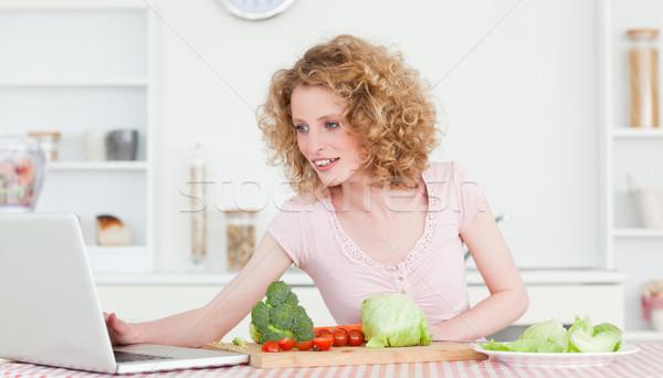 Iyi görünümlü sarışın kadın rahatlatıcı dizüstü bilgisayar pişirme sebze Stok fotoğraf © wavebreak_media