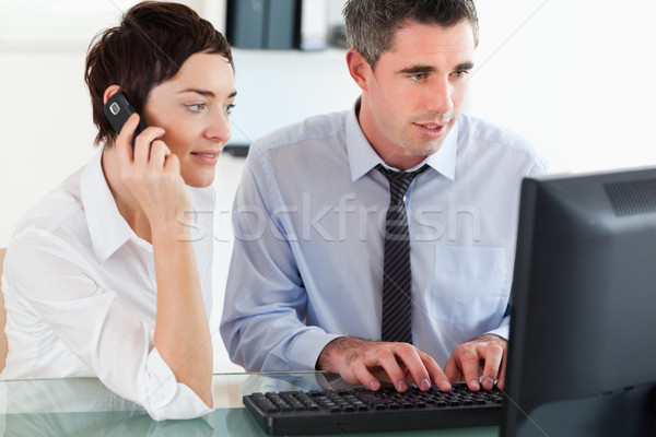 Woman telephoning while her colleague is using a computer in an office Stock photo © wavebreak_media