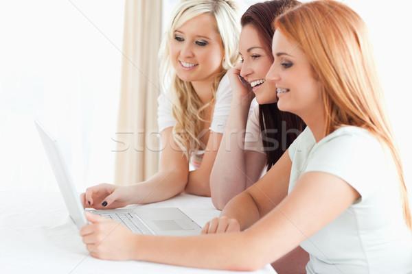Encantador mujeres sesión mesa portátil cocina Foto stock © wavebreak_media