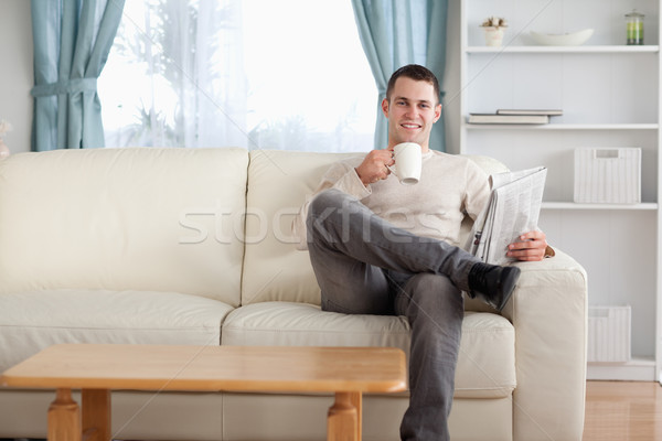 Man having a tea while reading the news in his living room Stock photo © wavebreak_media