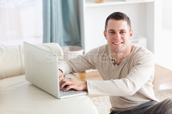 Smiling man sitting on a carpet posing with a notebook in his living room Stock photo © wavebreak_media