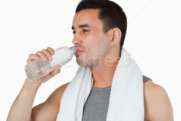 Young man taking a sip of water after workout against a white background Stock photo © wavebreak_media