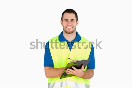 Smiling young delivery man completing delivery note against a white background Stock photo © wavebreak_media