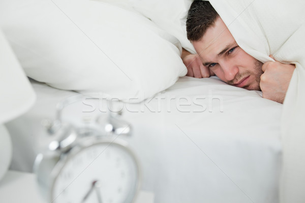 Tired man covering his ears while his alarm clock is ringing in his bedroom Stock photo © wavebreak_media