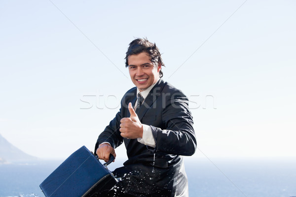 Cheerful businessman with the thumb up while holding a briefcase Stock photo © wavebreak_media