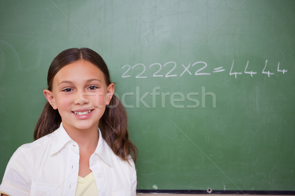 Stock photo: Schoolgirl posing in front of a chalkboard in a classroom