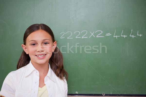 Schoolgirl posing in front of a chalkboard in a classroom Stock photo © wavebreak_media