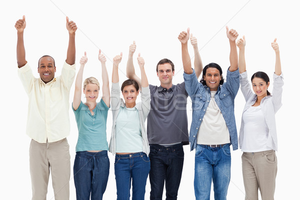 1a944694ab People raising their arms with the thumbs-up against white background Stock  photo © wavebreak_media