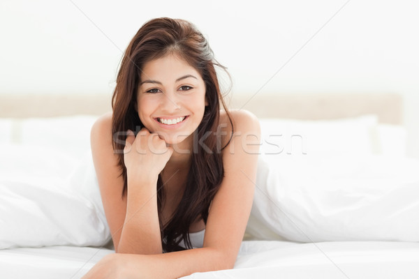 A woman lying at the end of the bed looking forward and smiling. Her hand against her chin with her  Stock photo © wavebreak_media