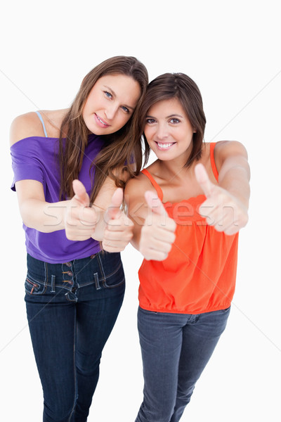 Stock photo: Teenagers putting their thumbs up with beaming smiles