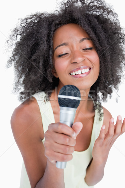 Concentrated young woman singing into a microphone against a white background Stock photo © wavebreak_media